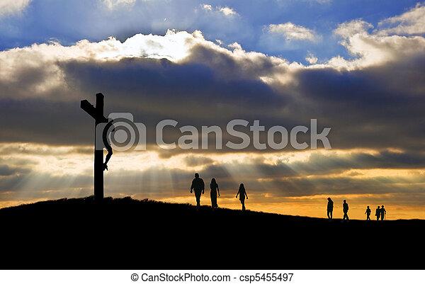 Silueta de Jesucristo crucifixión en cruz el Viernes Santo, la gente camina colina arriba hacia Jesús - csp5455497